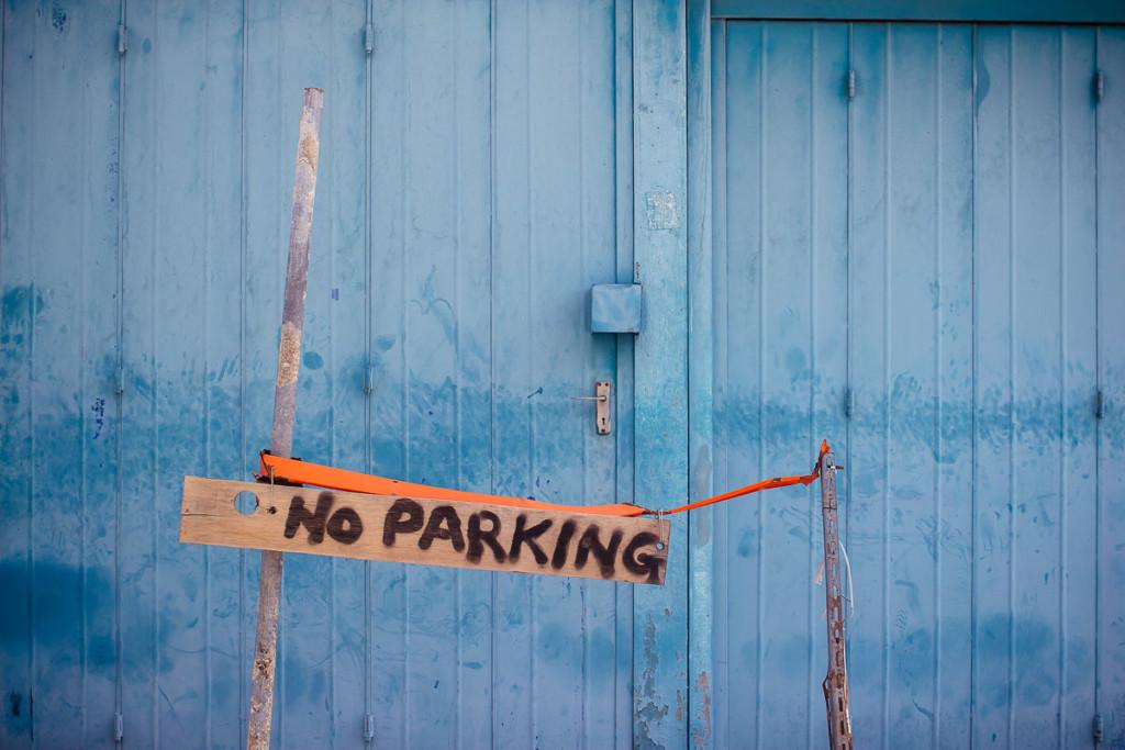 wooden no parking sign in front of blue doors