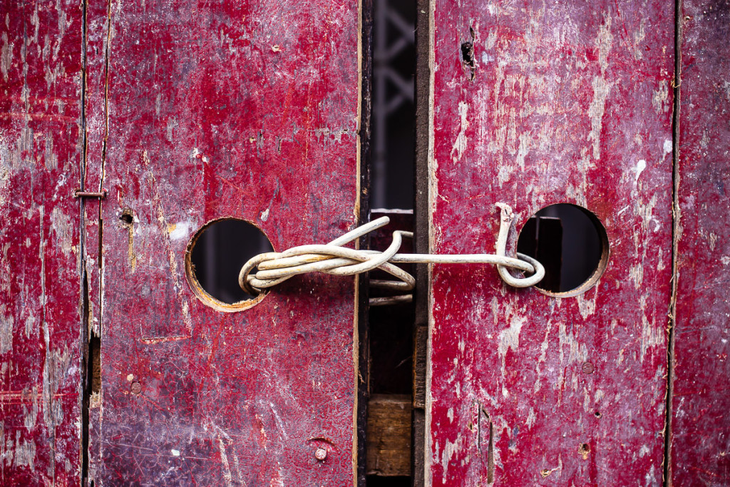 withered red wooded doors tied shut with cable