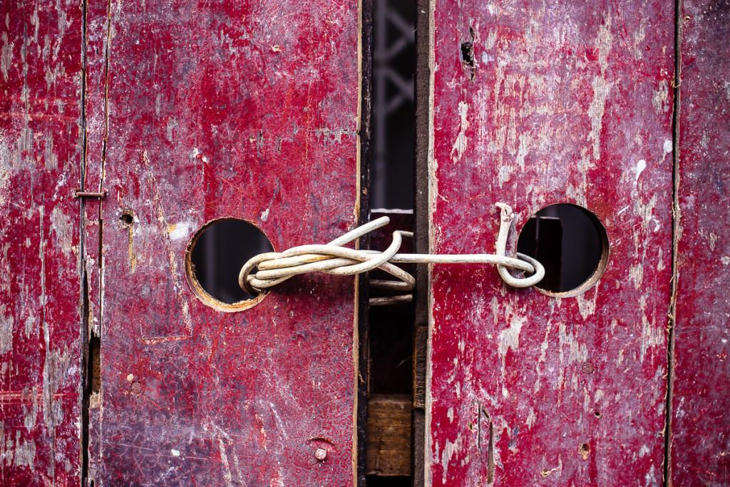 verwitterte, mit Draht zugebundene Holztüren in rot