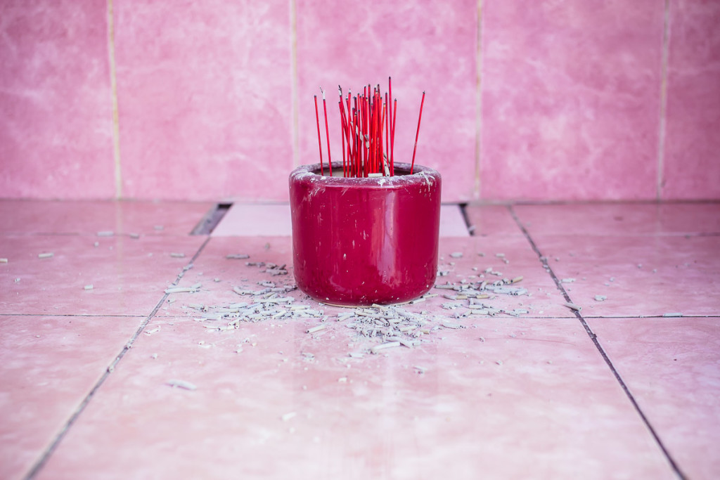 burnt incense sticks in red cup in front of pink tiles