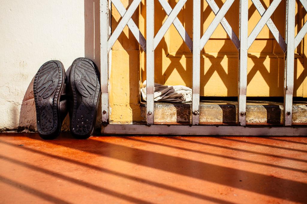 Schwarze Schuhe auf orangen Boden neben gelber Tür mit Metallgitter