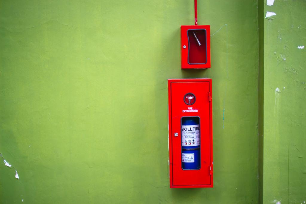 Blauer Feuerlöscher in roter Box an grüner Wand