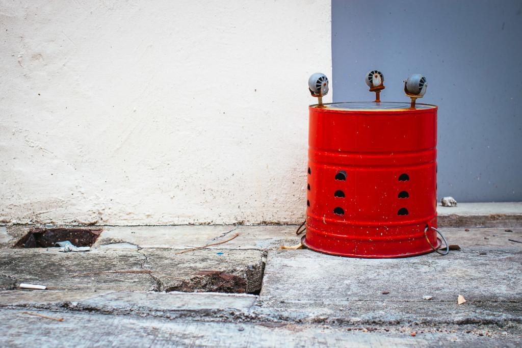 Umgekippter roter Eimer mit Rädern vor Wand in weiss und grau