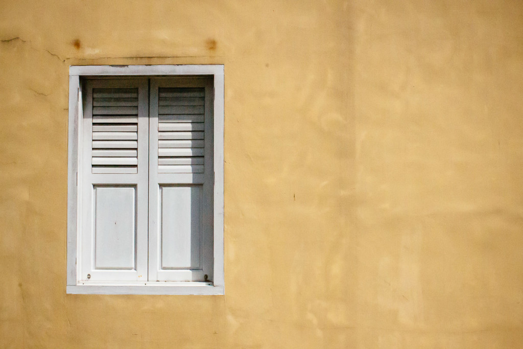 window with white blinds in yellow wall