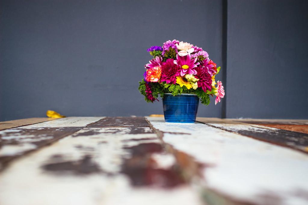 Kleine blaue Keramikvase mit Blumenstrauß auf weiß-braunem Holztisch vor grauem Hintergrund