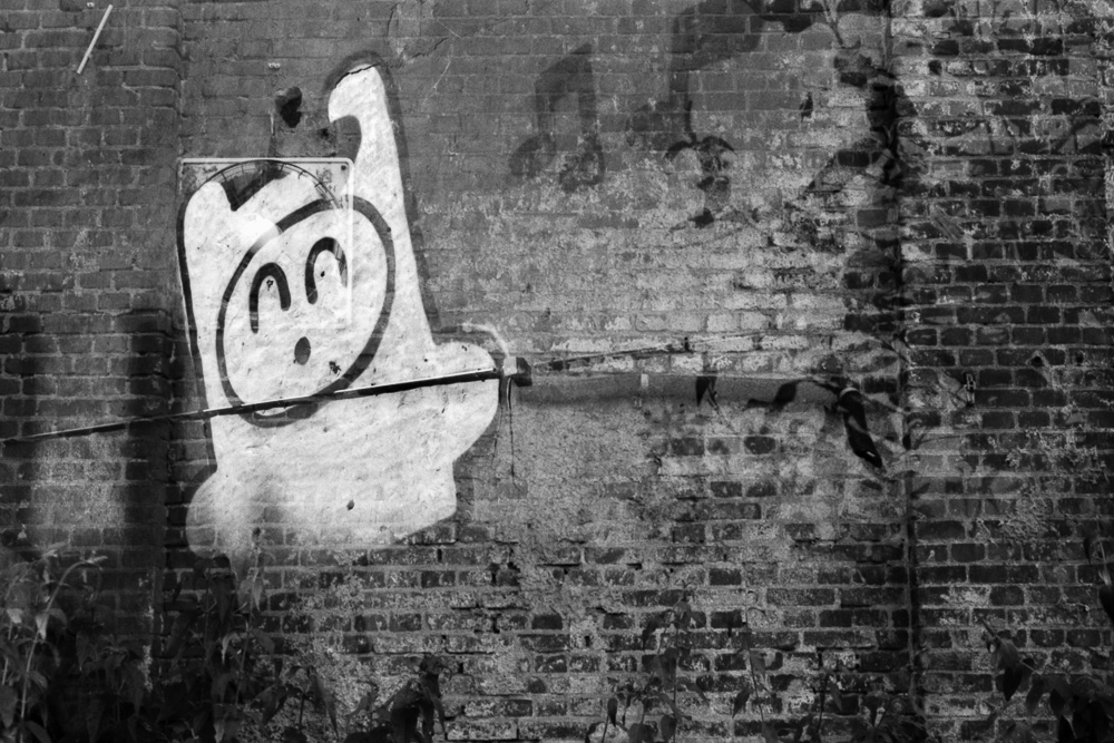 Double exposure of a cartoon graffiti on old brick wall