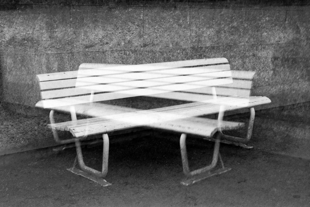 Double exposure of a white bench near a wall